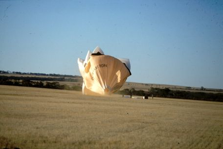 A hot air balloon shaped as the Sydney Opera House has landed and the envelope begins to fall.
